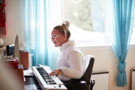 Disabled young woman playing piano at home