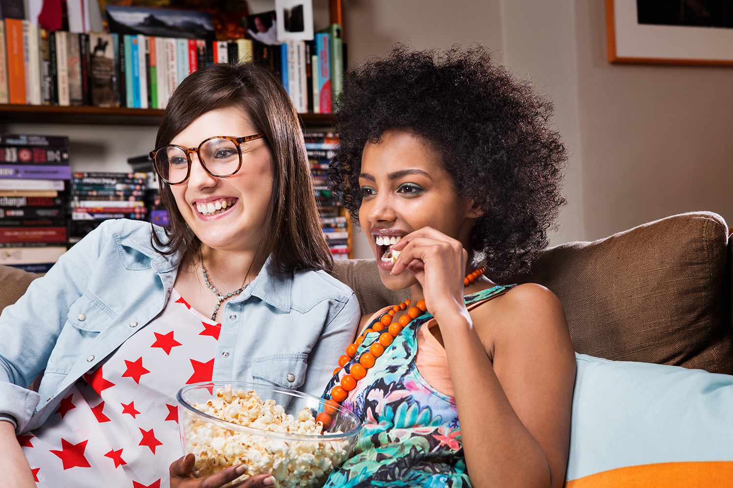 Two women watching a documentary in a living room