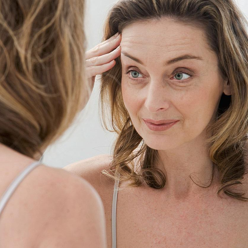 Woman looking in mirror at lines on face