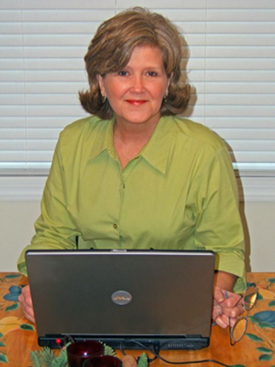 A woman in a green shirt sitting behind a computer