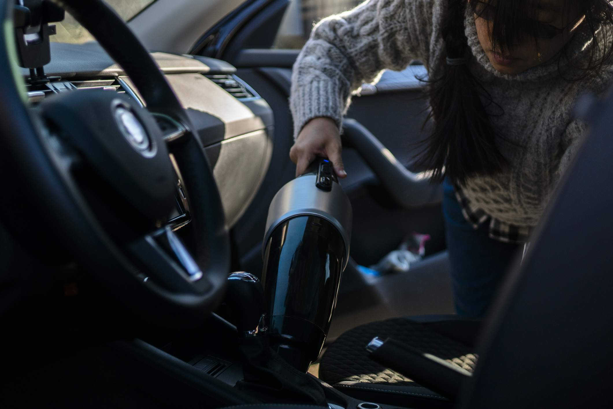 girl cleaning car with portable cleaner