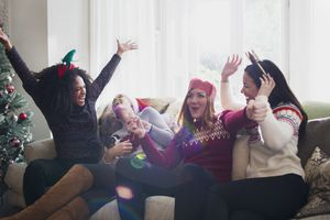 Laughing friends celebrating Christmas on sofa