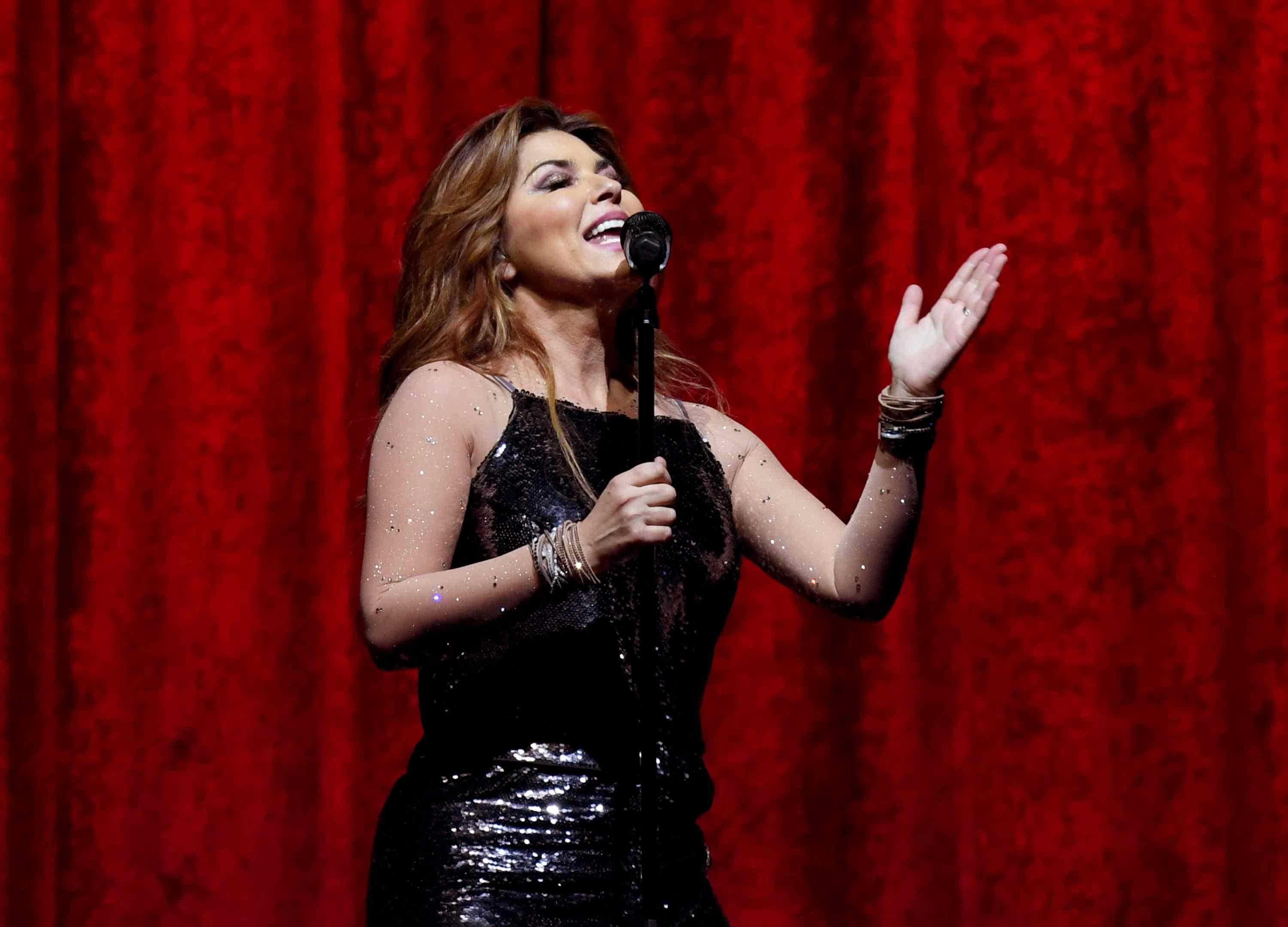 Shania Twain performing in front of a red curtain on stage.