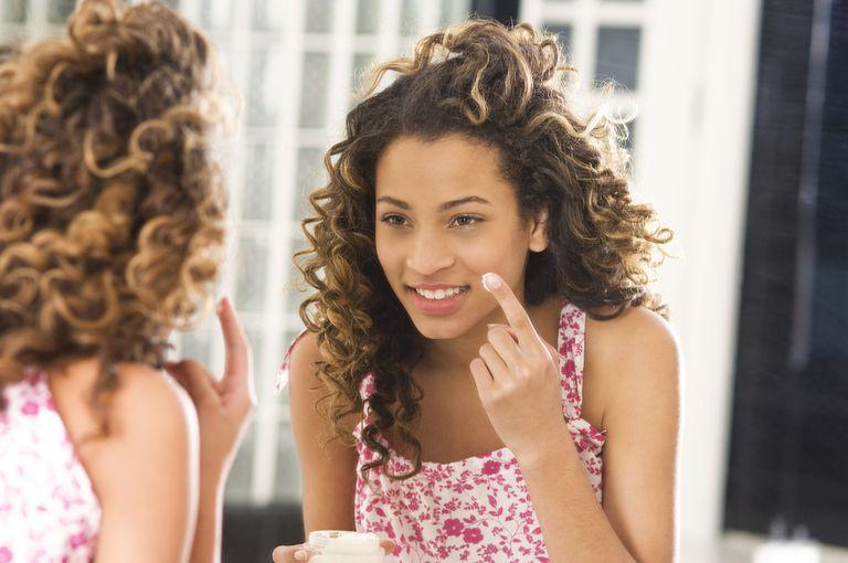 Girl applying moisturizer on her face