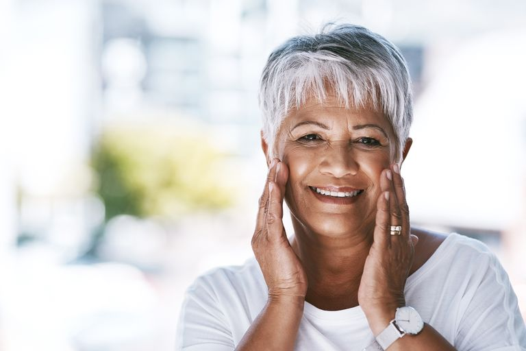 Mature African-American woman in a white t-shirt, wearing a watch and touching her face