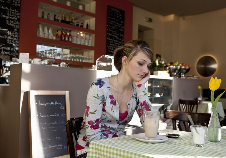 Woman alone in cafe looking disappointed