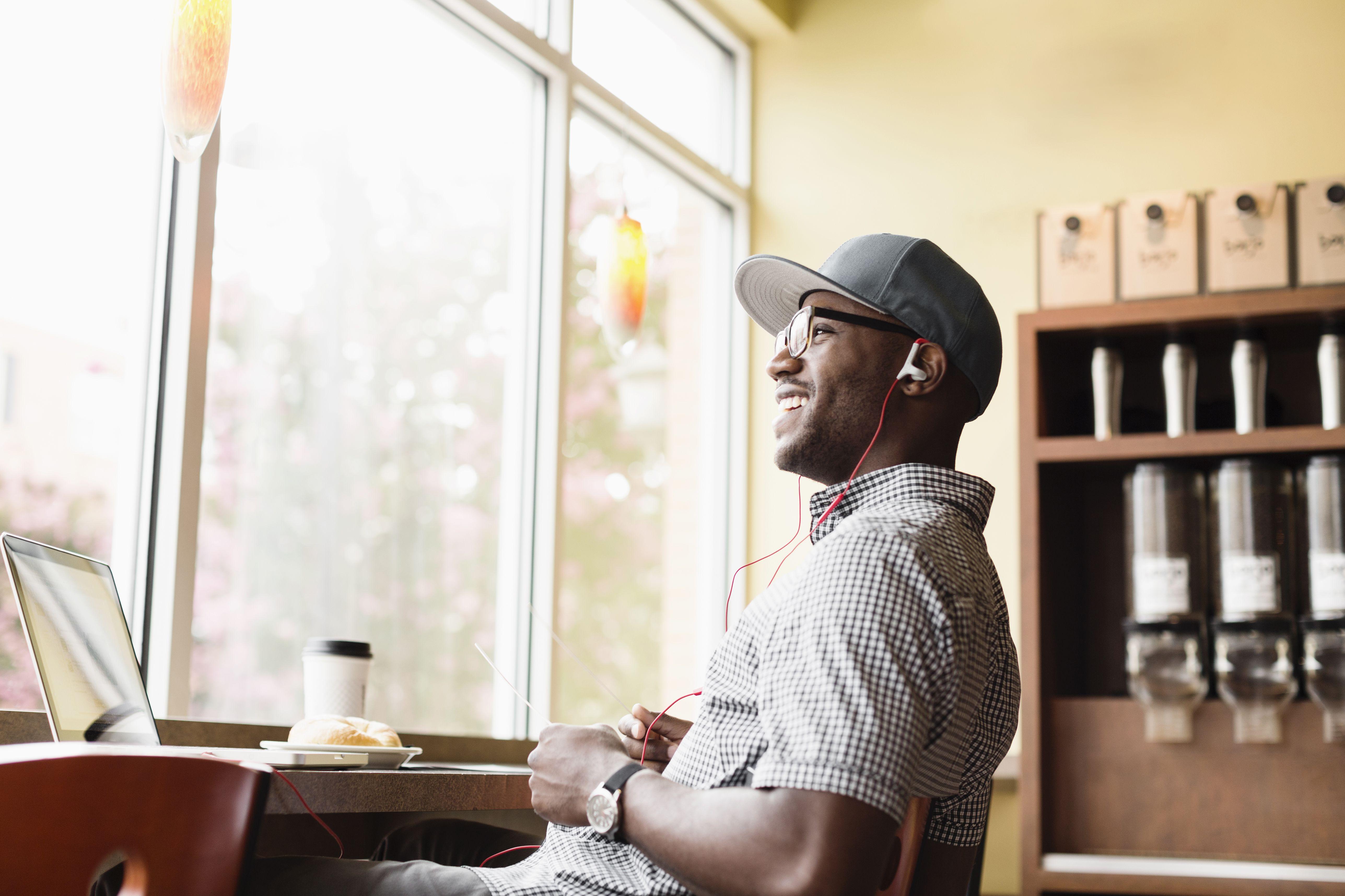 Laughing Black man using laptop in coffee shop