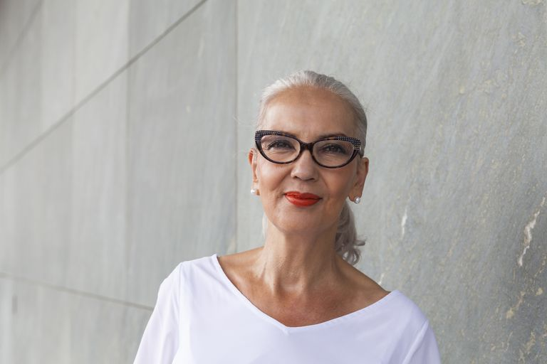 Mature white woman wearing red lipstick, horn-rimmed glasses, a white top, and pearl earrings, with her hair pulled back