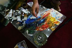 An Iraqi painter dabs his brush on a palette