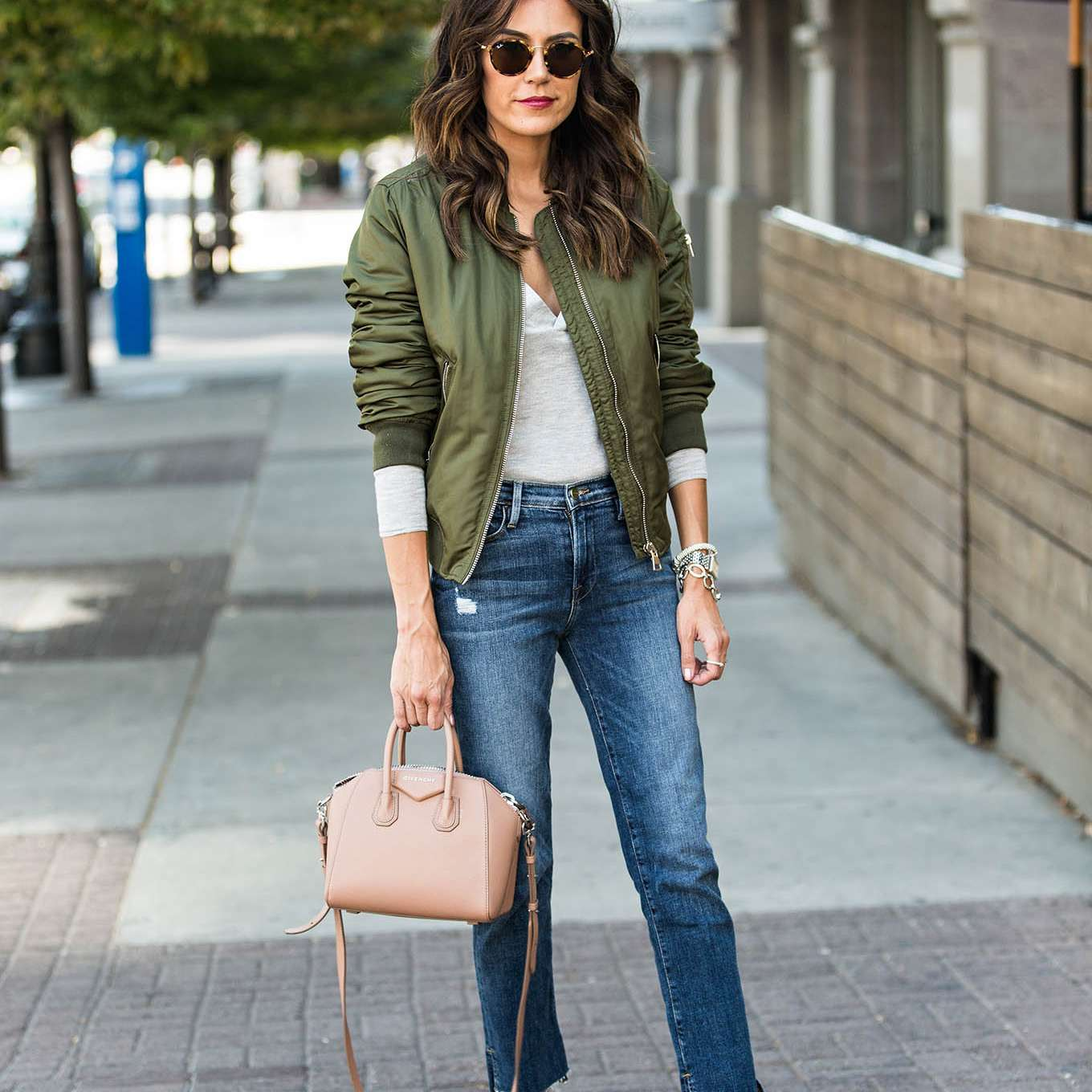 Street style woman in olive green jaket and jeans for fall