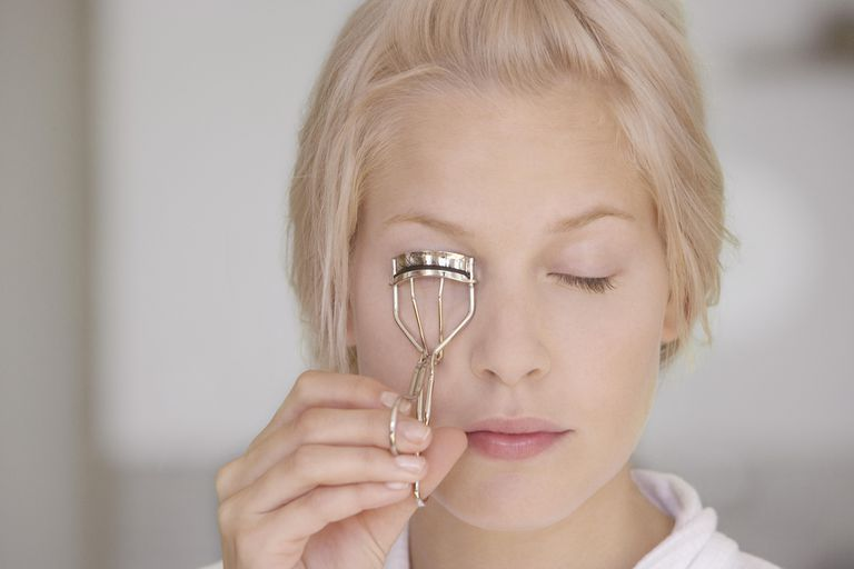 Young woman using eyelash curler, eyes closed