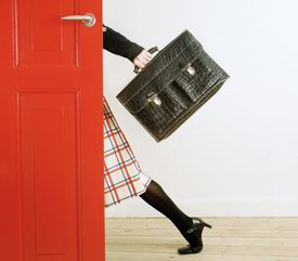 a side profile of a woman walking out the door carrying a purse