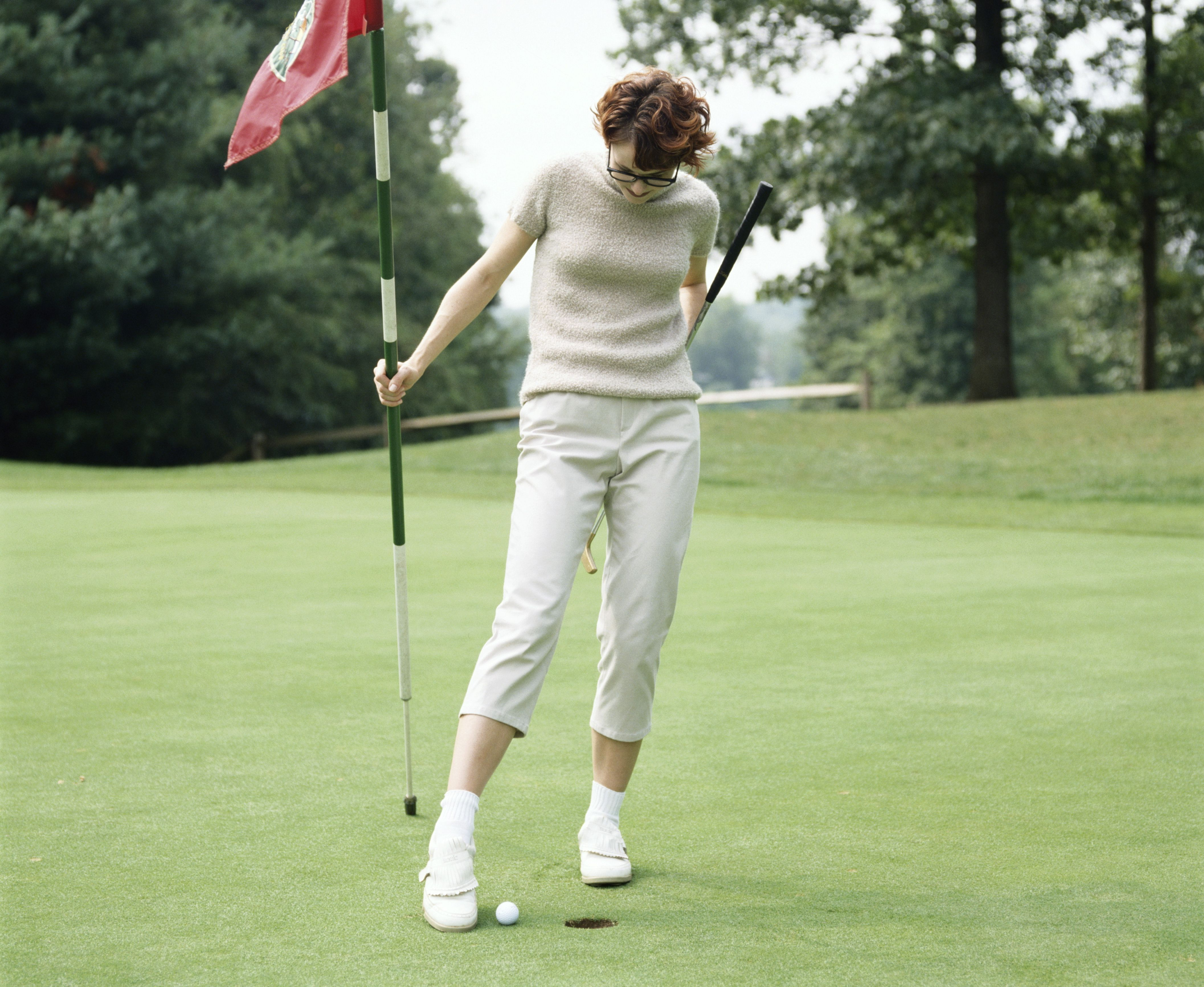 woman using her foot to knock golf ball into hole