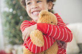 boy hugging Teddy Bear in front of Christmas tree