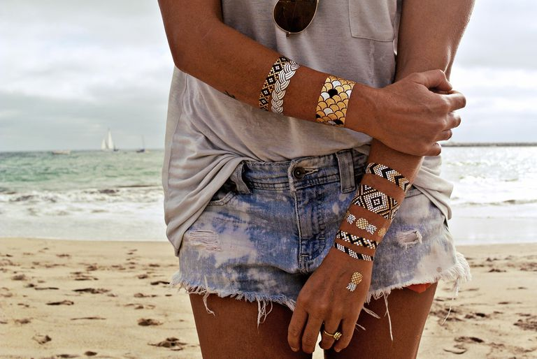 Close-up of Flash Tattoos on woman's wrists with the beach and ocean in the background