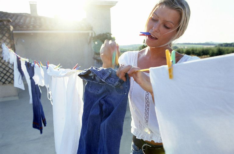Woman hanging jeans to dry outside with clothespins