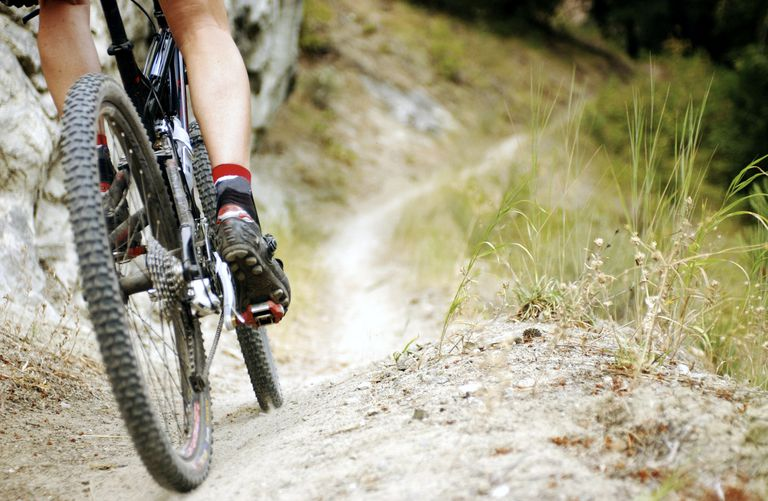 Close up of mountain bike tires and pedals on trail