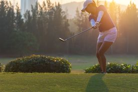 woman golf player in action of end downswing of wood driver, after hit the golf ball away from tee off to the fairway ahead, sunset scenery in background