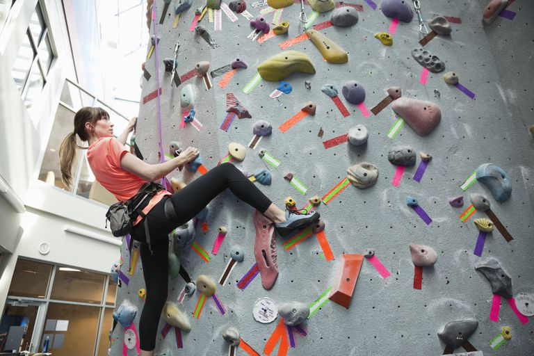 woman rock climbing indoors