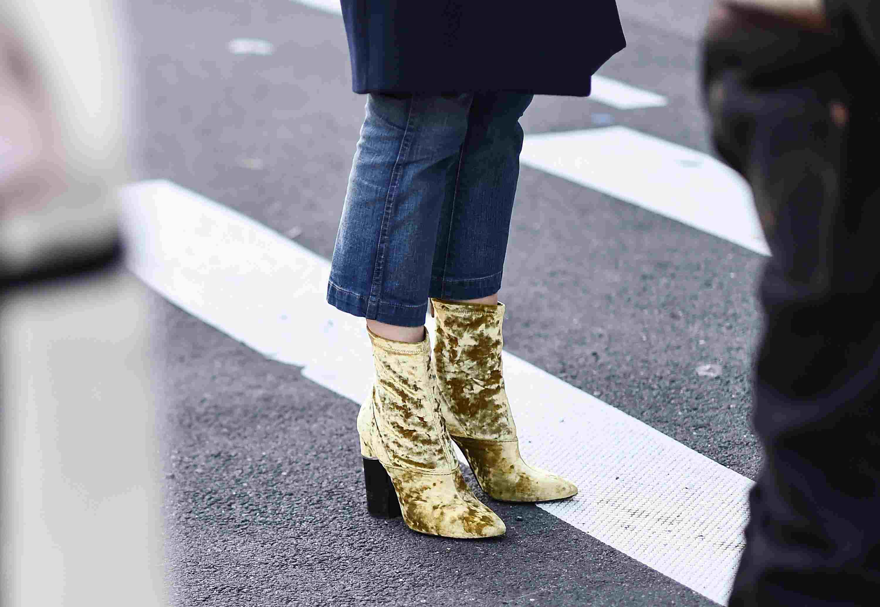 Woman's legs in jeans and gold ankle boots
