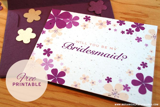 A purple floral Will You Be My Bridesmaid? card on a table