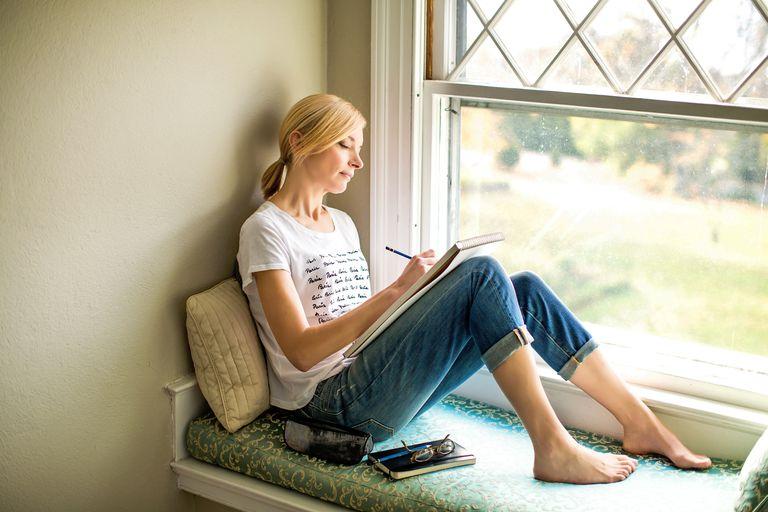 woman journaling in window