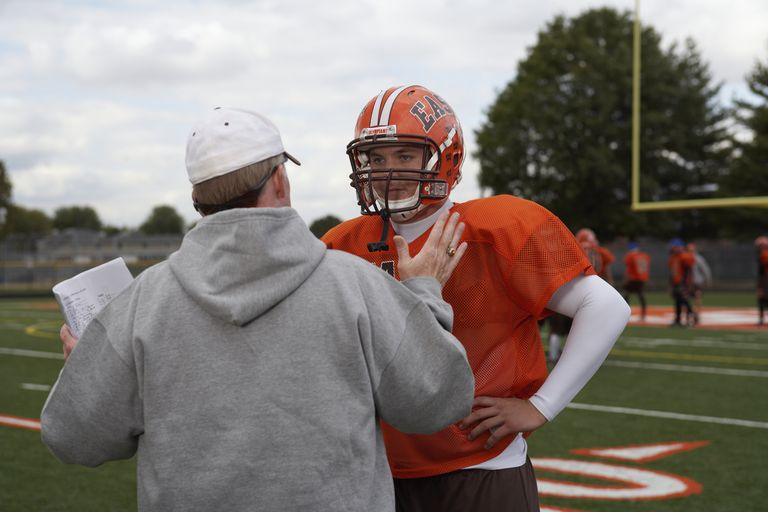 Teenage American football player talking to coach