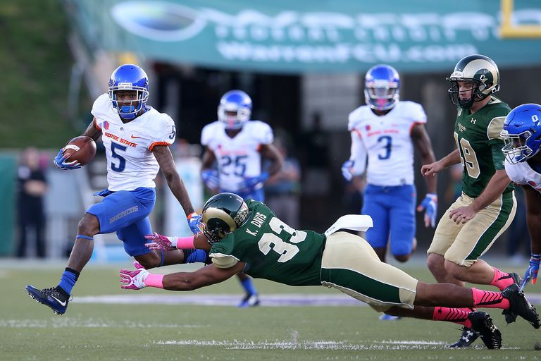 Donte Deayon #5 of the Boise State Broncos eludes Kevin Davis #33 of the Colorado State Rams as he returns a punt at Sonny Lubick Field at Hughes Stadium on October 10, 2015 in Fort Collins, Colorado
