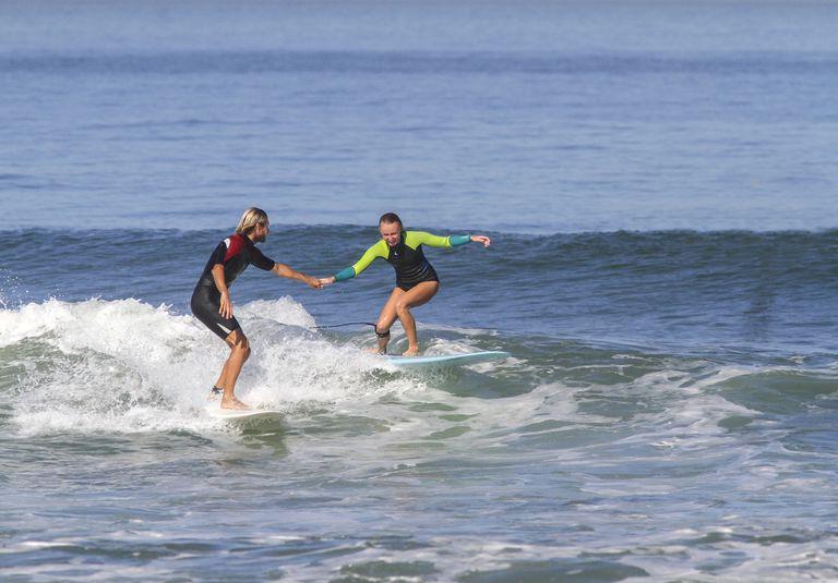 Man helping woman on surfboard