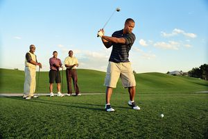 Male golfer driving ball, friends watching (blurred motion).