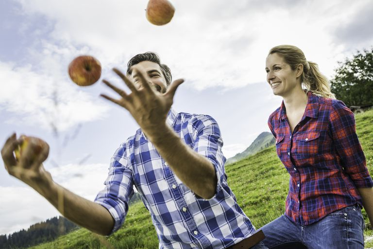 man juggling apples next to woman
