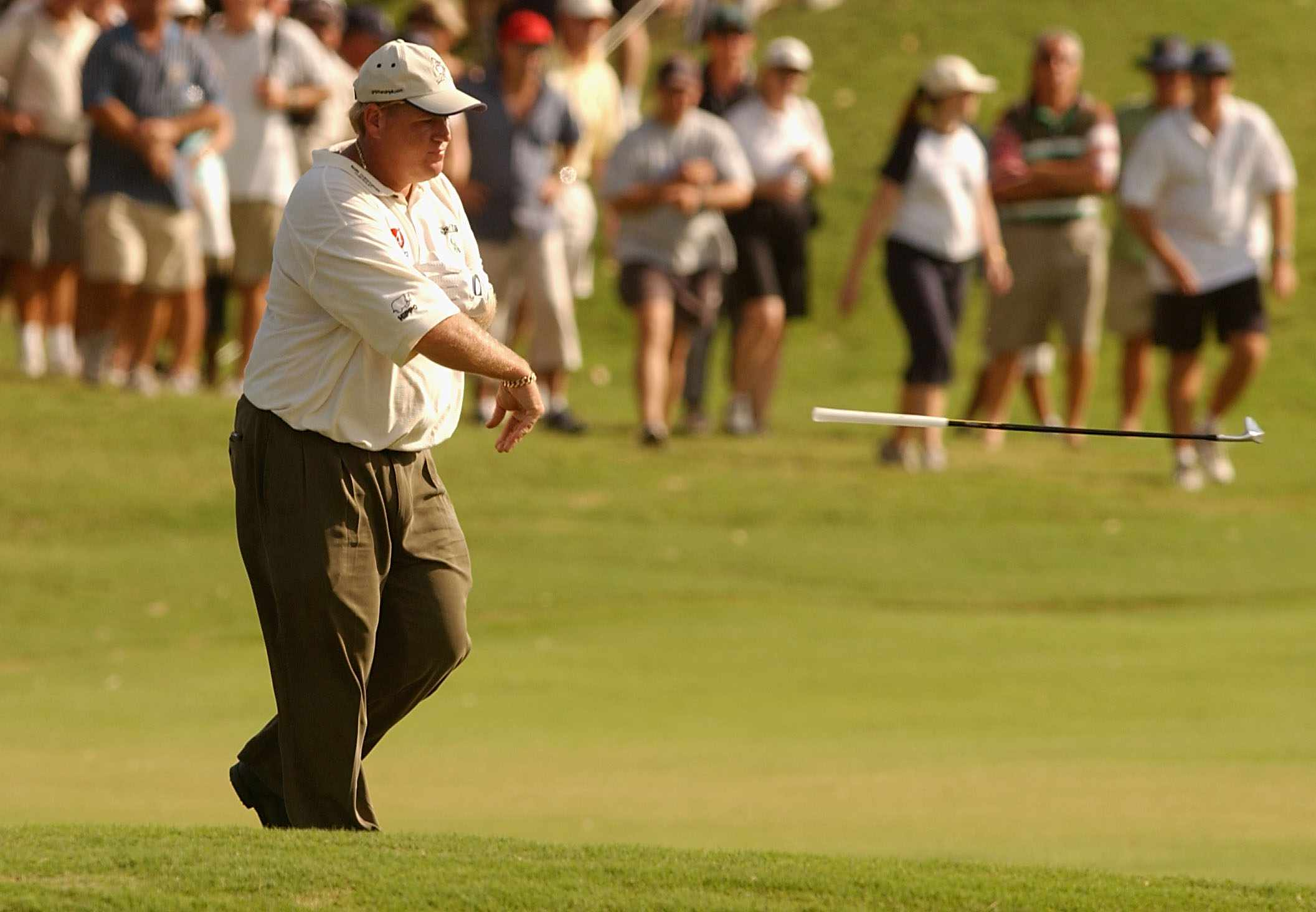 John Daly of the USA throws his iron after having to take a drop when his approach shot hit an officials cart and ran into the water on the 13th hole during round two of the Australian PGA Championships at the Hyatt Regency Golf Course, Sunshine Coast, Australia on November 29, 2002.