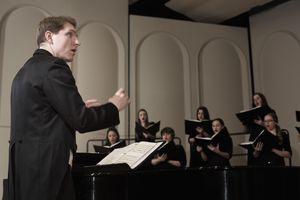 Choir Director leading choir on stage