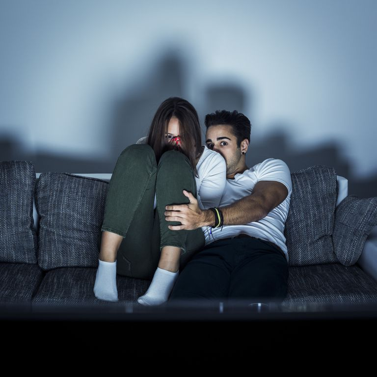 Young couple watching horror movie.