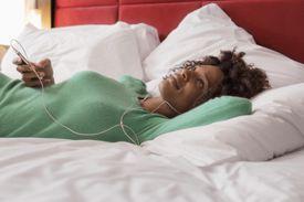 Woman listening to earphones on bed