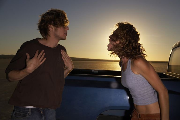 Couple arguing by truck in desert landscape, sunset
