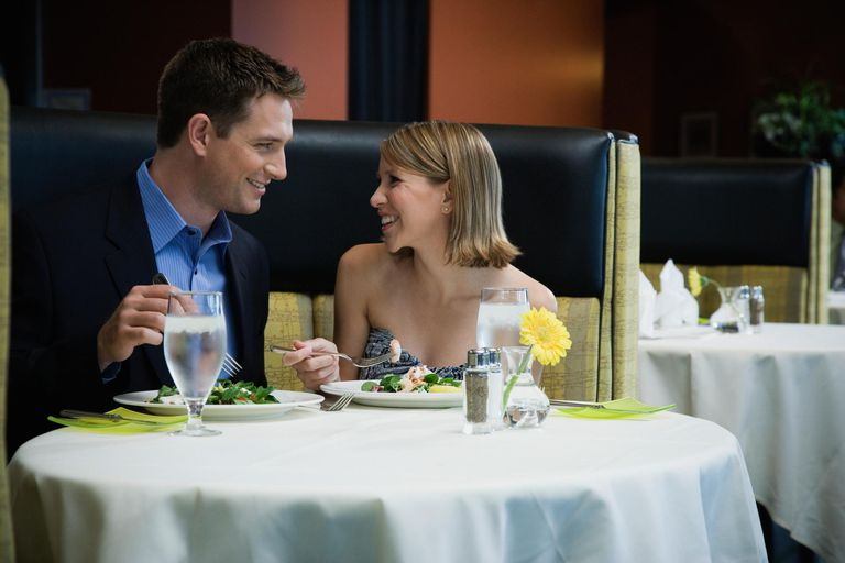 Couple eating in restaurant, smiling together.