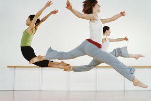 Three female dancers practicing in dance studio, leaping