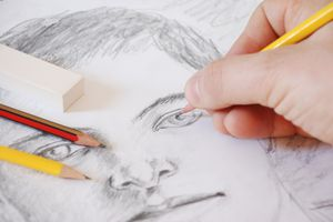 Hand holding pencil sketching the face of a young boy