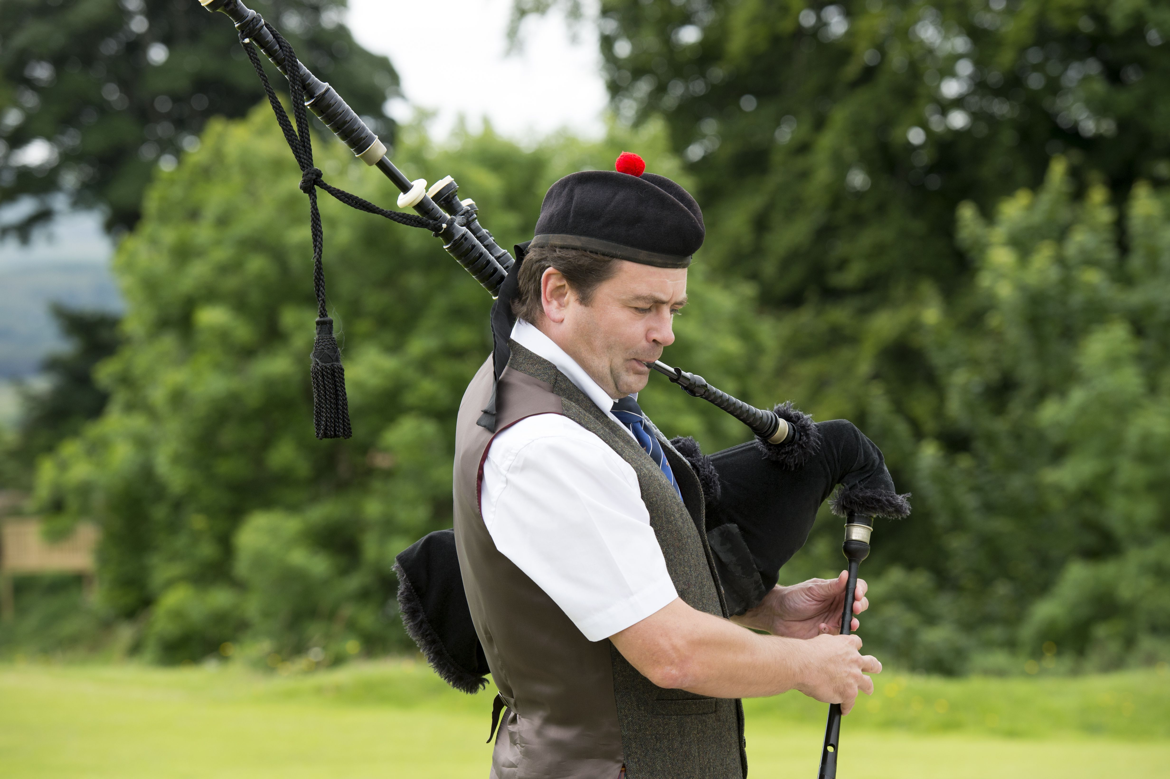 A young man playing Great Highland Bagpipe during the summer Highland games at Tobermory