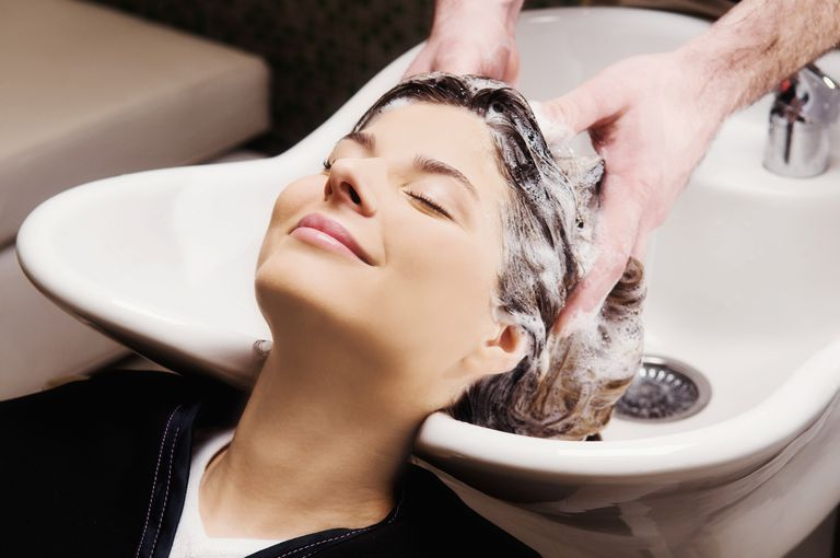 Young woman getting hair shampooed at salon