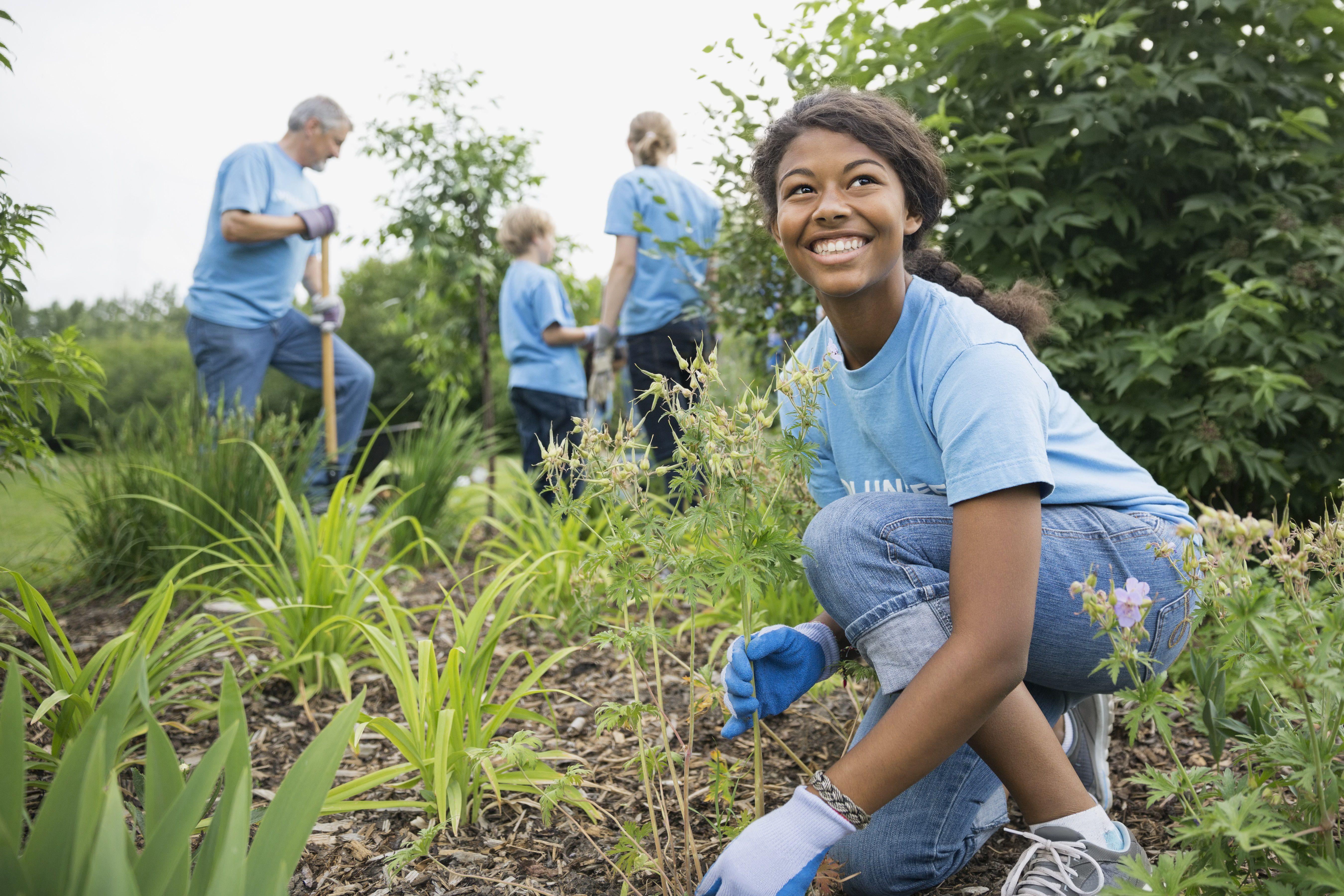 Smiling girl working in garden