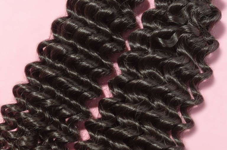 Deep curly black human hair weaves extensions bundles upon pink background