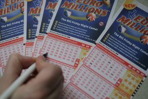 Picture of a hand filling out Euromillions Lottery tickets.
