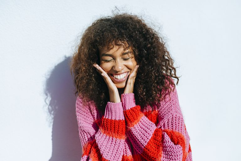 Woman smiling with curly hair smiling against baby blue wall