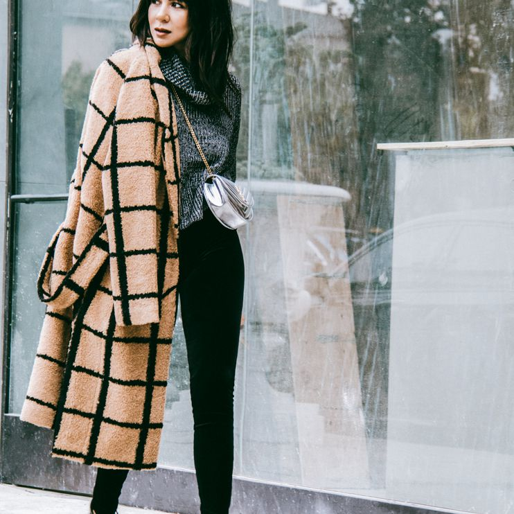 Woman in checked coat and black pants