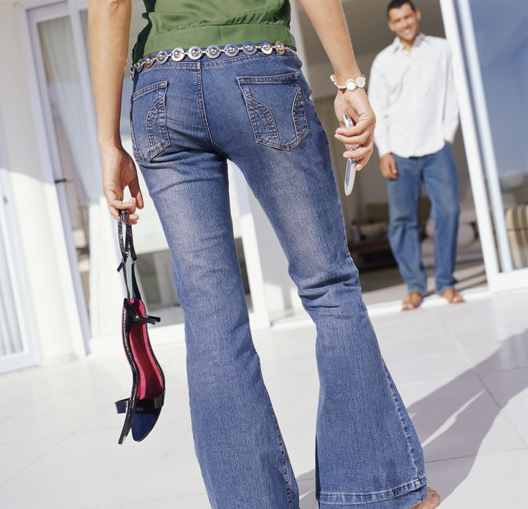 woman wearing bellbottom jeans holding shoes