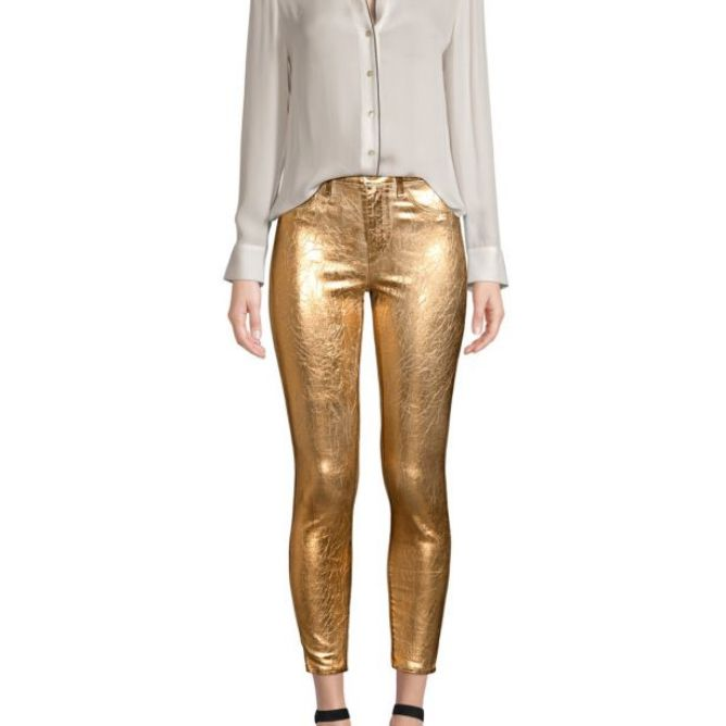 Woman wearing white blouse and gold jeans