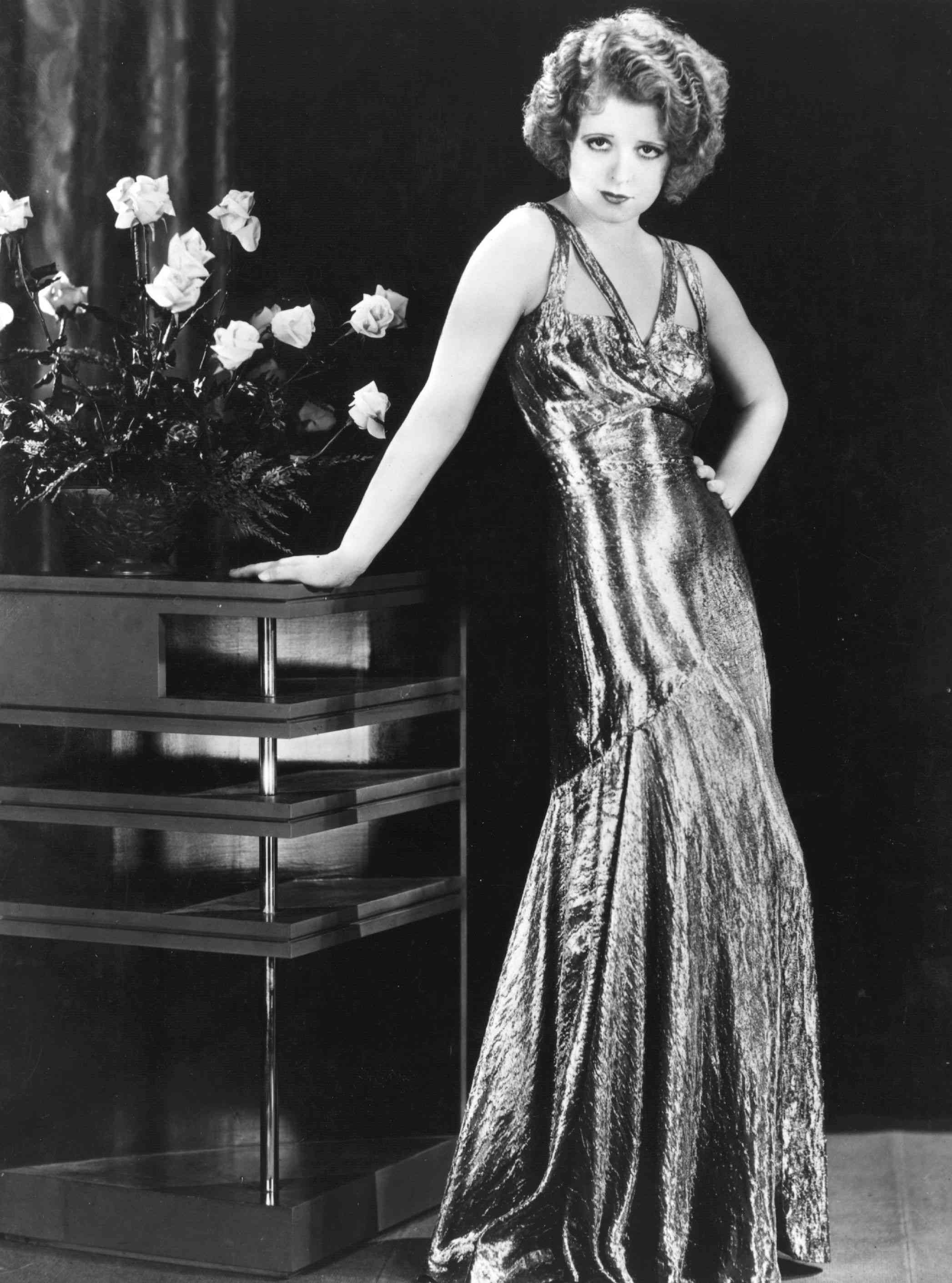 Silent screen siren Clara Bow (1905 - 1965) popularly known as the 'It' girl, wears a silver lame dress for the Paramount film 'No Limit', directed by Frank Tuttle.