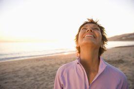Mature woman at beach looking at sky